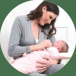 Mutter stillt ihr Baby mit Cosyme Schlafsack